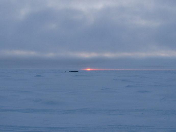 Солнце опускается за горизонт, скоро наступит полярная ночь. Темными пятнами видны топливные депо