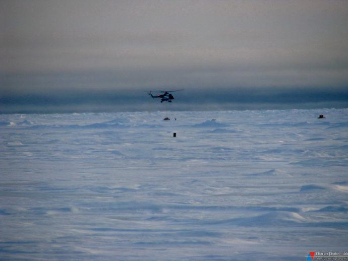Начало грузовых операций, вдали виден груз, доставленный вертолетом